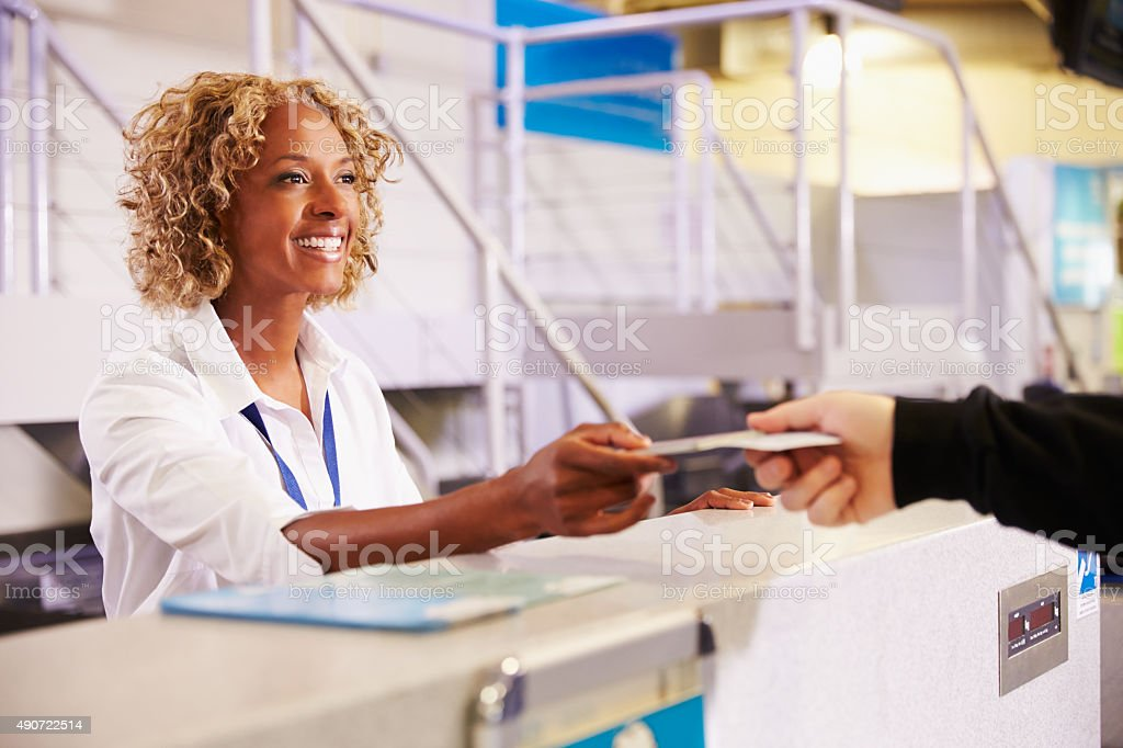 Staff At Airport Check In Desk Handing Ticket To Passenger stock photo
