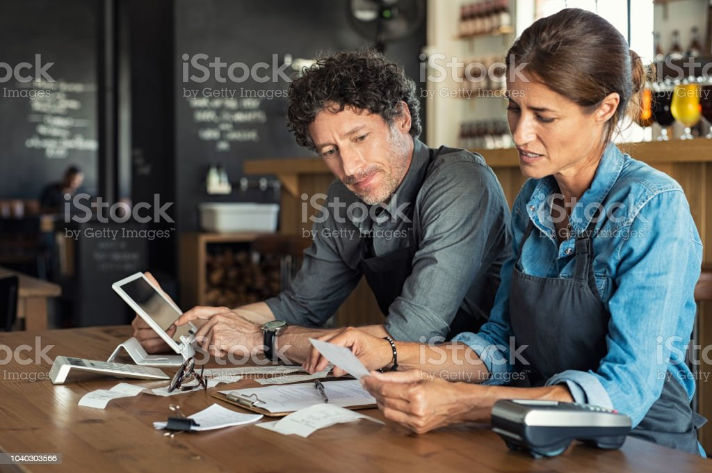 Staff calculating restaurant bill Man and woman sitting in cafeteria discussing finance for the month. Stressed couple looking at bills sitting in restaurant wearing uniform apron. Café staff sitting together looking at expenses and bills. Accountancy Stock Photo