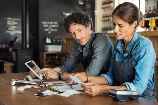 Staff calculating restaurant bill Man and woman sitting in cafeteria discussing finance for the month. Stressed couple looking at bills sitting in restaurant wearing uniform apron. Café staff sitting together looking at expenses and bills. expense stock pictures, royalty-free photos & images
