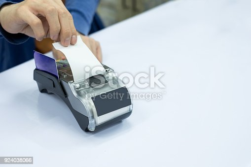 914593772istockphoto Staff cashier rip bill paper with card on payment terminal 924038066