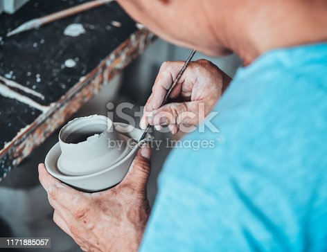 A senior man is decorating a porcelain clay in a ceramic factory in China.