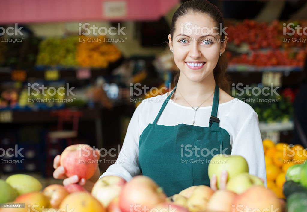 Staff in apron selling apples stock photo