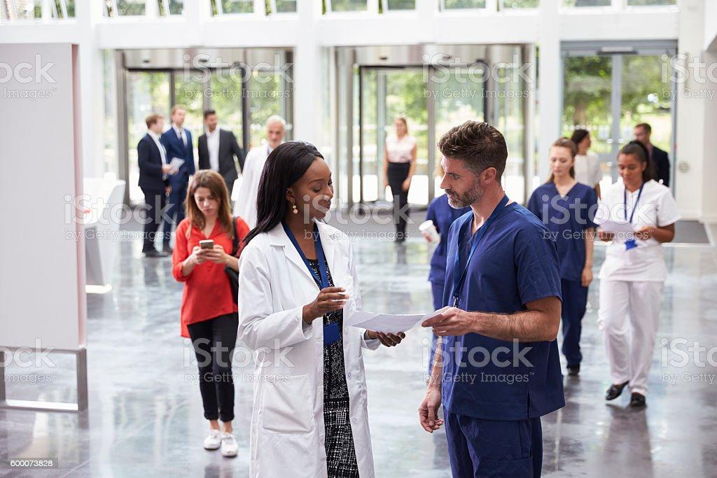 Staff In Busy Lobby Area Of Modern Hospital - foto de acervo