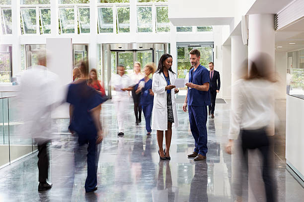 staff in busy lobby area of modern hospital - hospital stock pictures, royalty-free photos & images