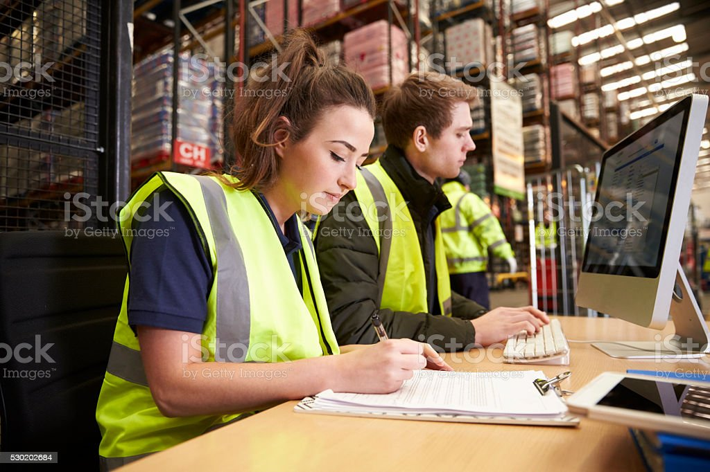 Staff managing warehouse logistics in an on-site office stock photo