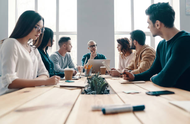 Staff meeting. Group of young modern people in smart casual wear discussing something while working in the creative office staff meeting stock pictures, royalty-free photos & images