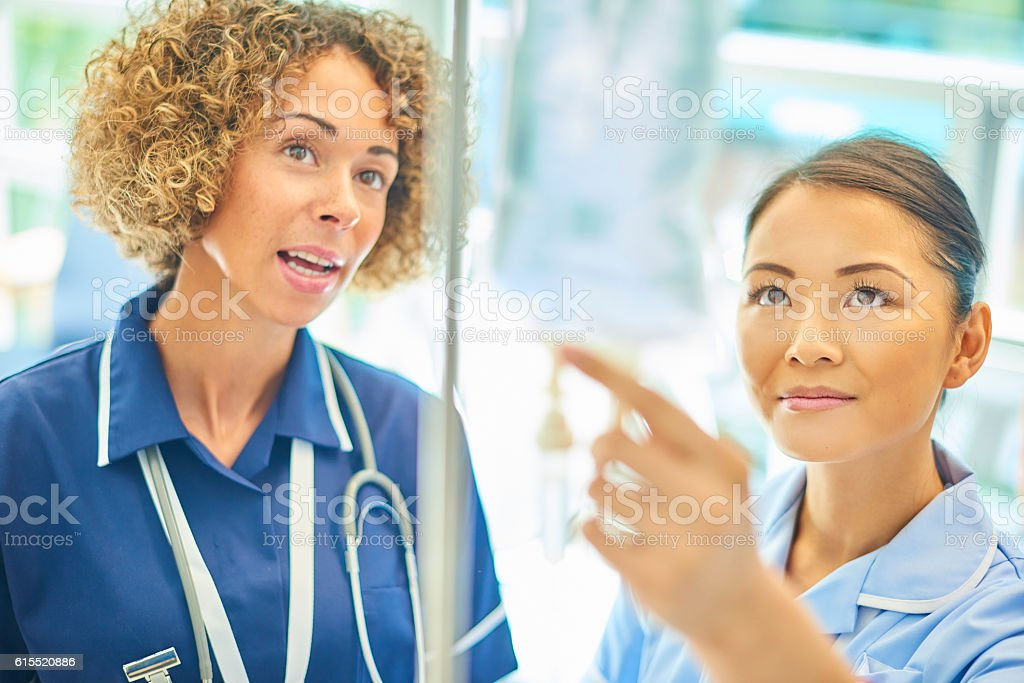 staff nurse advising young nurse stock photo