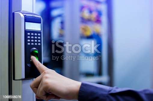 istock Staff push down electronic control machine with finger scan to access the door of control room or data center. 1068548076