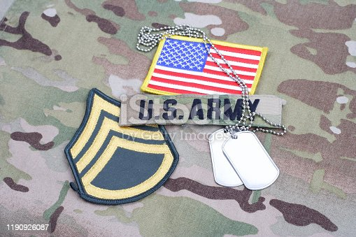 istock US ARMY Staff Sergeant rank patch, flag patch, with dog tag on camouflage uniform 1190926087