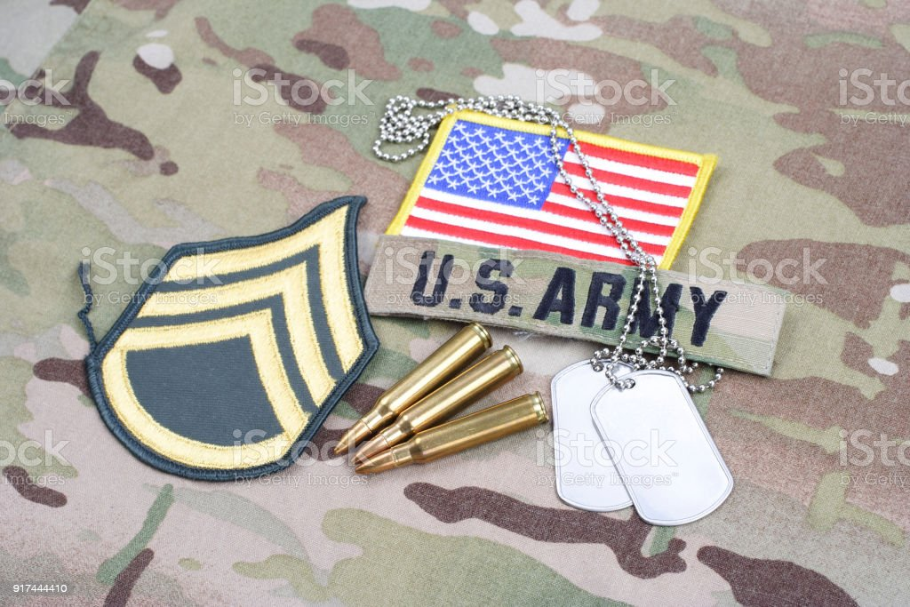 US ARMY Staff Sergeant rank patch, flag patch, with dog tag with 5.56 mm rounds on camouflage uniform stock photo