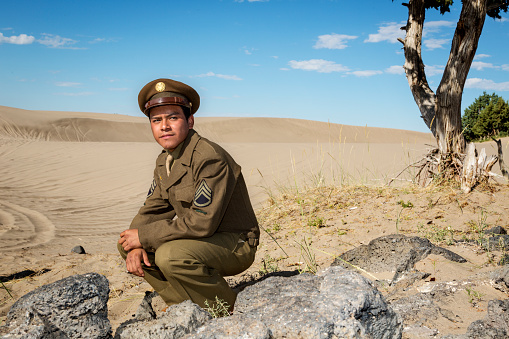 US Staff Sergeant in authentic World War II uniform rests in the desert sand.