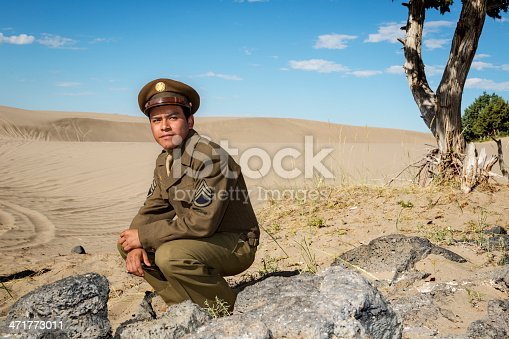 US Staff Sergeant in authentic World War II uniform rests in the desert sand.
