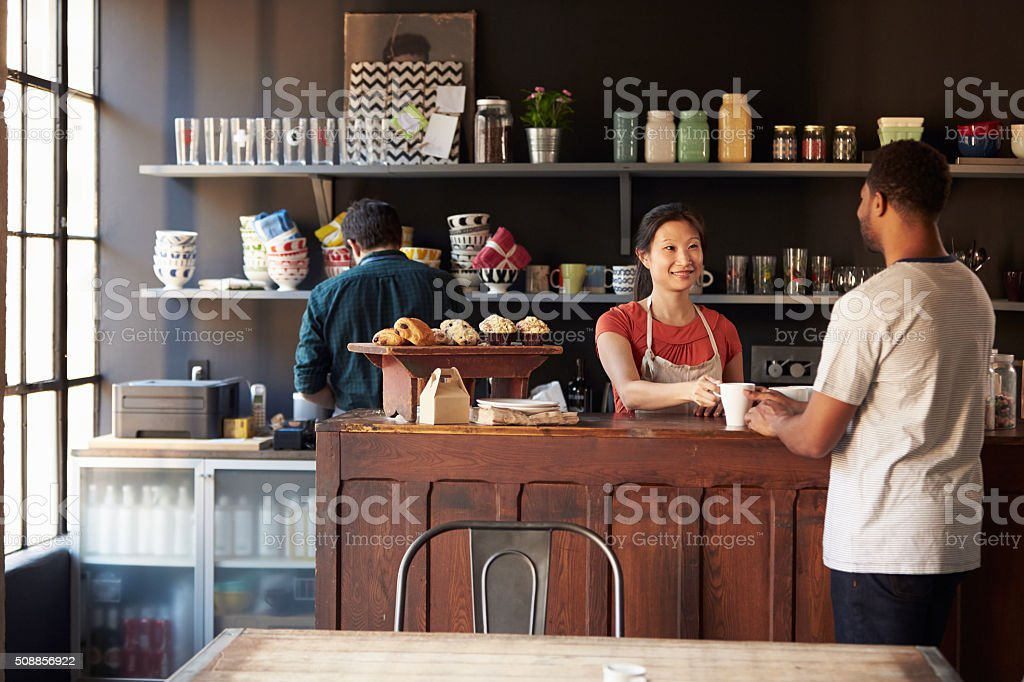 Staff Serving Customer In Busy Coffee Shop stock photo