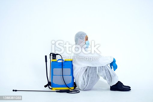 Staff spray disinfectant at the building. He wearing PPE suit. Hygiene service concept.