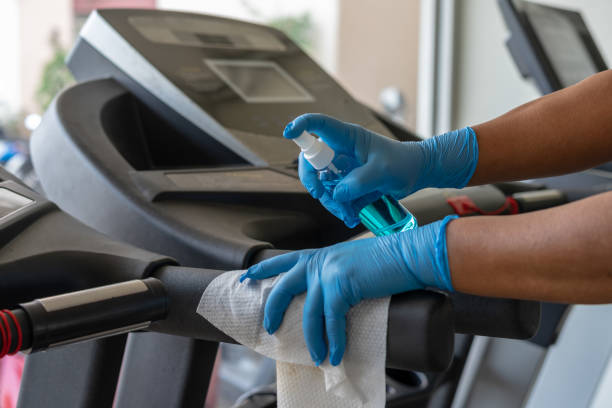 staff using wet wipe and a blue sanitizer from the bottle to clean treadmill in gym. antiseptic,disinfection ,cleanliness and healthcare, anti corona virus (covid-19). - тренажер стоковые фото и изображения
