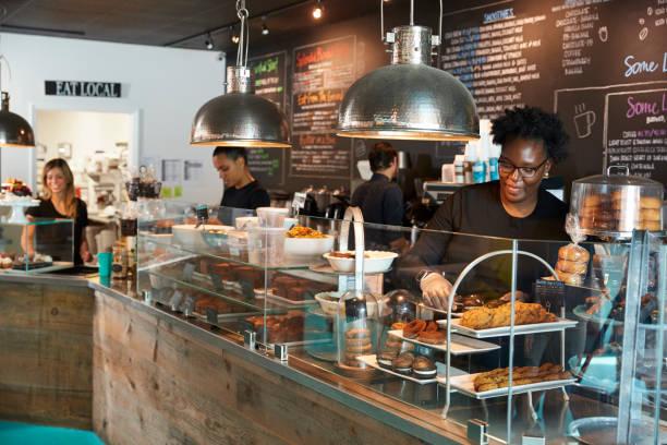 mitarbeiter hinter der theke in belebten café - coffee shop stock-fotos und bilder