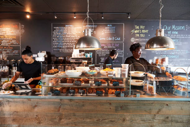 mitarbeiter hinter der theke in belebten café - cafe stock-fotos und bilder