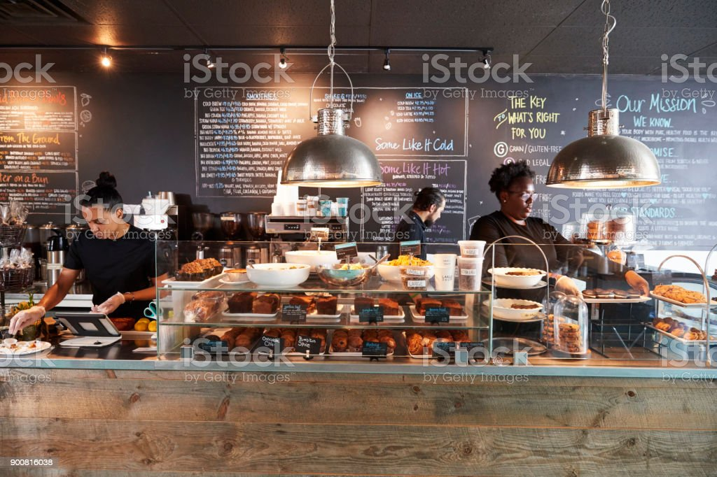 Staff Working Behind Counter In Busy Coffee Shop stock photo