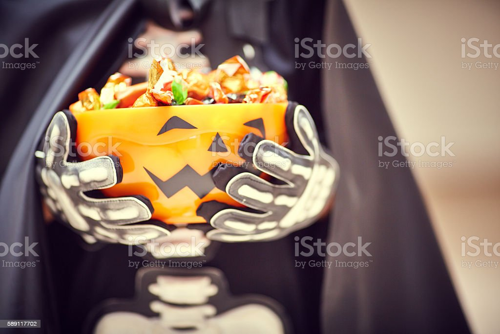Stage costume and Halloween bowl with trick or treat candies stock photo