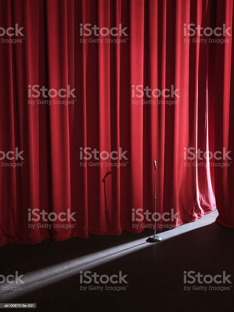 Stage curtains slightly open, letting beam of light onto microphone stand royalty-free stock photo