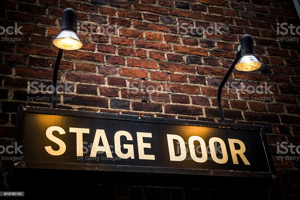 Stage door sign lit by spotlights at theatre venue stock photo
