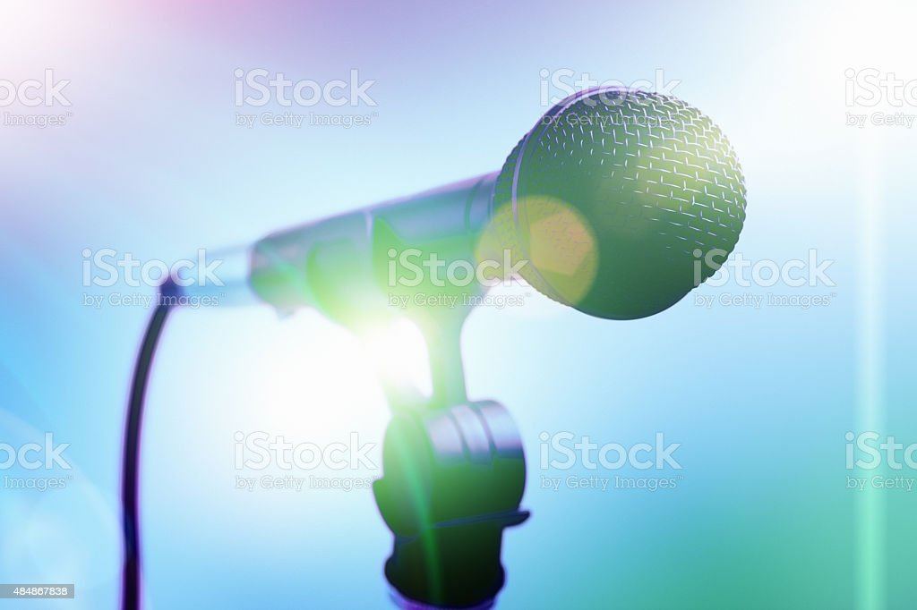 Stage footlights light up vocal mic on stand stock photo