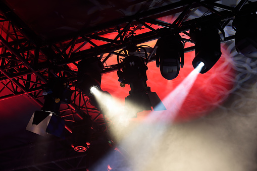 Stage lighting truss with multiple spotlights. Moving head spotlights hanging on a truss.