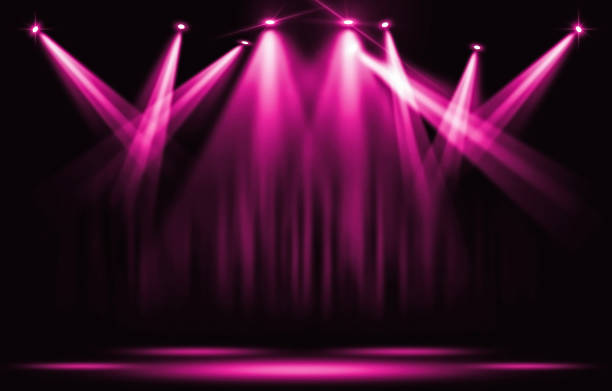 Stage lights. Pink violet spotlight with certain through the darkness. stock photo
