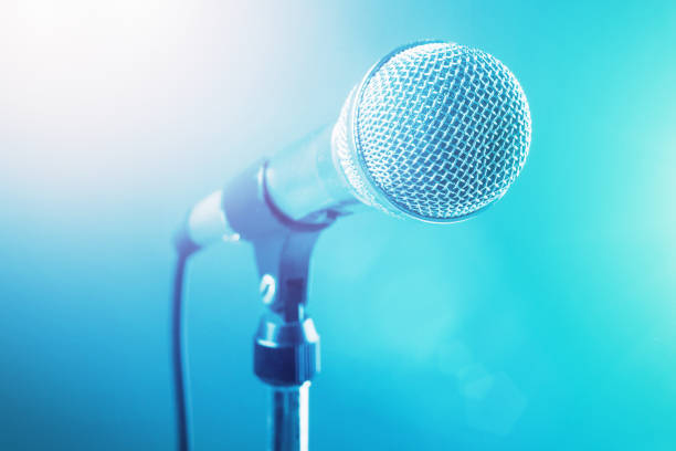 Stage microphone bathed in blue spotlights stock photo