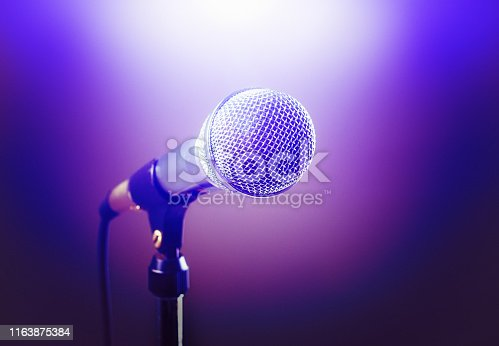 A dramatically lit stage microphone, purple spot lit in white.