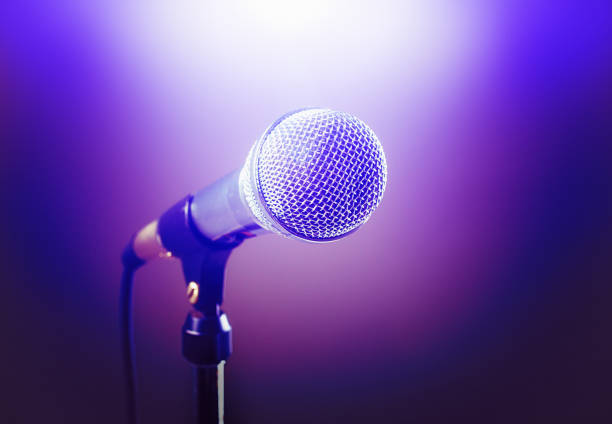 Stage microphone dramatically lit in purple and spot lit in white stock photo