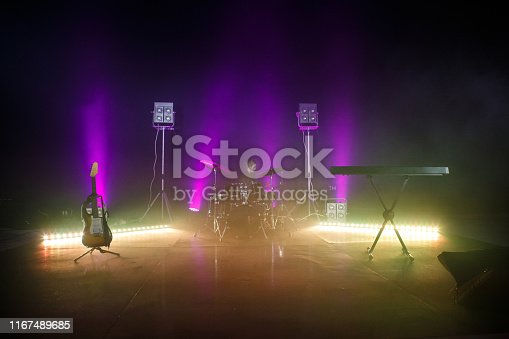 Wide shot of a stage set with instruments, lights and smoke ready for a rock concert.