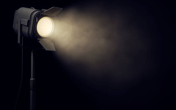 Stage spotlight in dark background Warm stage spotlight shines in dark background spot lit stock pictures, royalty-free photos & images