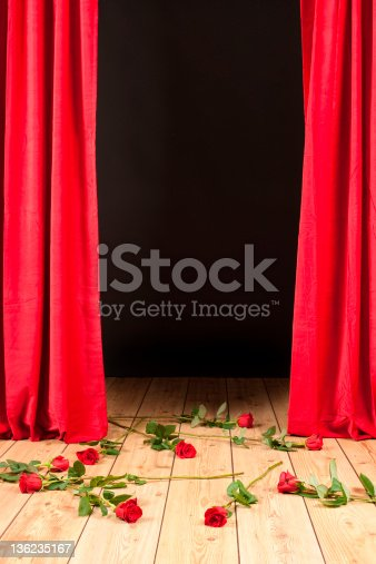 istock Stage with red curtains closing and red roses thrown 136235167