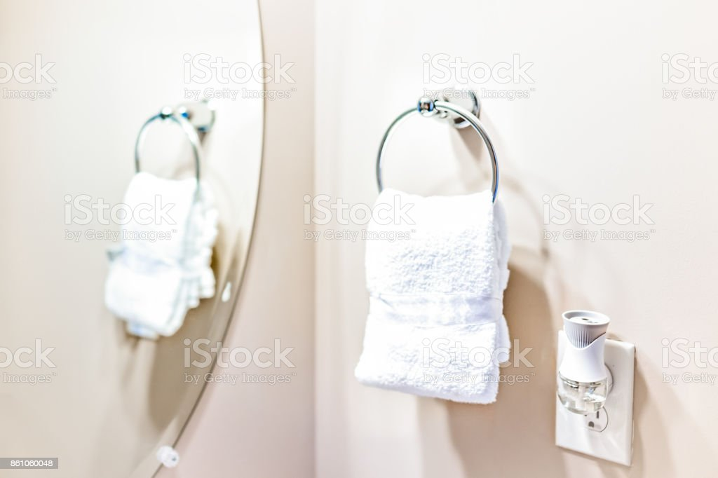 Staging modern bathroom with one small white towel hanging on rack in model home, apartment or house with air freshener and mirror reflection stock photo
