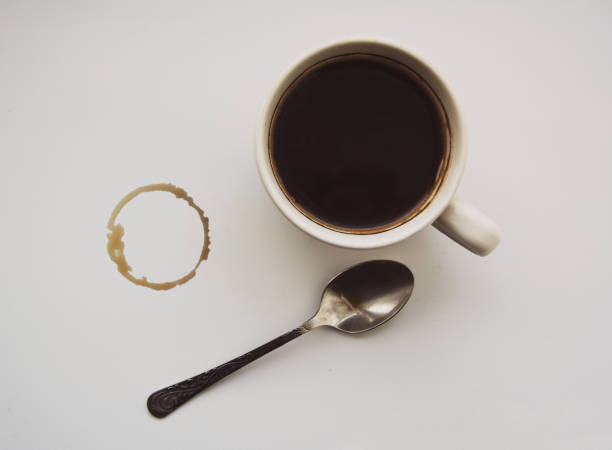 Stain from a cup of coffee, black coffee and a little spoon, white background stock photo