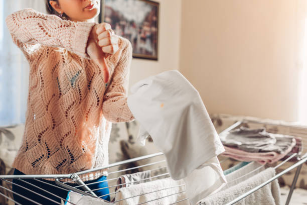 Stain of dirt on clothes. Woman found spot on shirt after washing and shows thumb down. Bad washing powder Stain of dirt on clothes hanging it on dryer. Woman found spot on shirt after washing and shows thumb down. Bad washing powder wet clothing women t shirt stock pictures, royalty-free photos & images