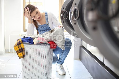 Young woman notices a stain on her sweatshirt at a laundromat. About 25 years old, Caucasian female.
