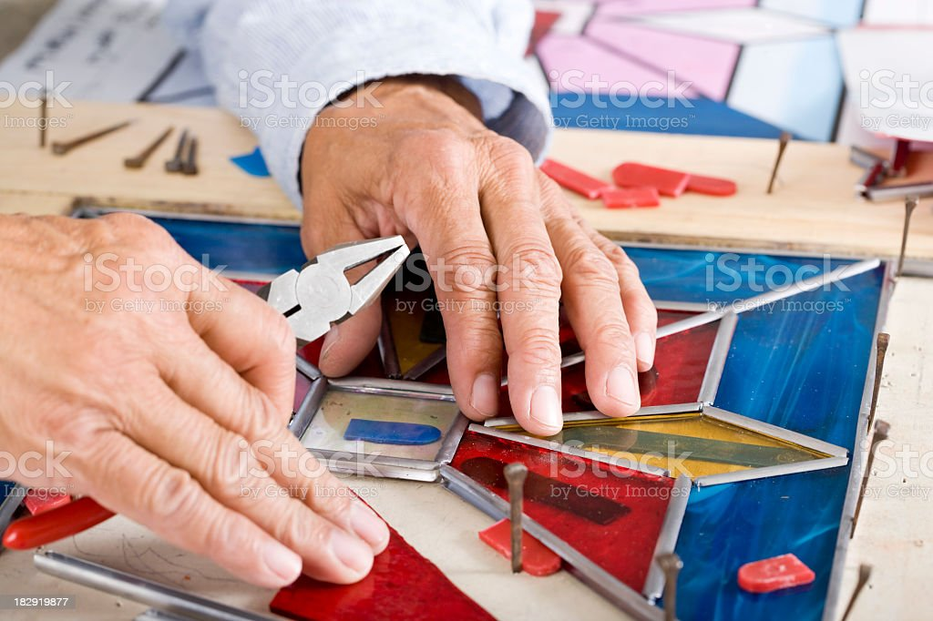 Stained glass craftsman working on project royalty-free stock photo