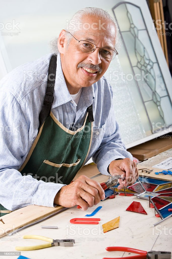Stained glass craftsman working on project stock photo