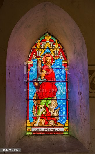 Beautiful stained glass in arched church window, or illuminated wall decoration, showing man dressed in red outfit France 2015