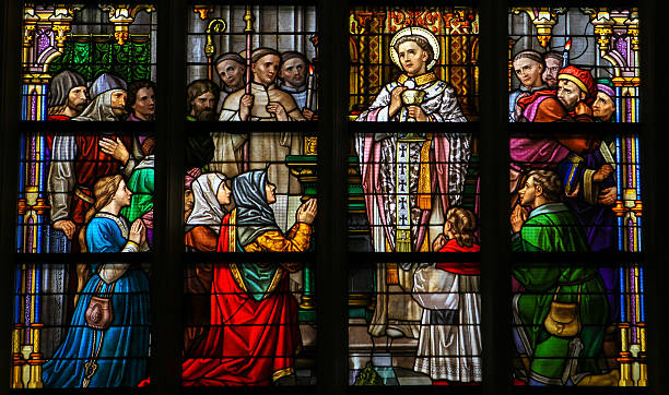 Stained Glass of Holy Communion in Den Bosch Cathedral Stained Glass Window depicting a saint performing the sacrament of Holy Communion in Den Bosch Cathedral, North Brabant, The Netherlands. This window was created more than 110 years ago, no property release is required. religious saint stock pictures, royalty-free photos & images