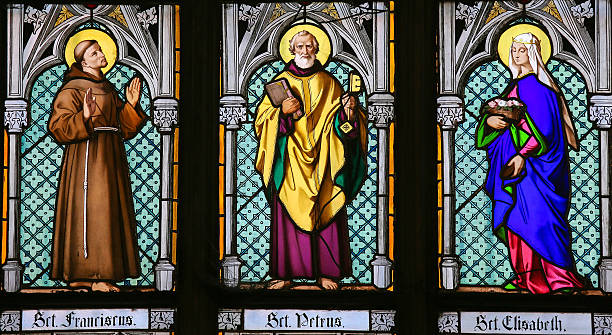 Stained Glass - Saints Francis, Peter and Elisabeth Prague, Czech Republic - April 2, 2016: Stained Glass window in St. Vitus Cathedral, Prague, depicting Saint Francis, Saint Peter and Saint Elisabeth religious saint stock pictures, royalty-free photos & images