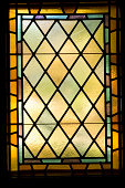 Soft light shines through an isolated stained glass window, dating to the early 1900's.