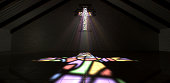 An interior building with a colorful stained glass window in the shape of a crucifix with a spotlight rays penetrating through it reflecting the image on the floor