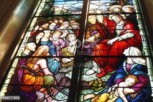 Charleston, SC, USA - March 12, 2011:  A stained glass window depicting Jesus preaching to a crowd of people.  It  is located in the Cathedral of St. John the Baptist in downtown Charleston. The Cathedral began construction in 1890 and opened in 1907. The stained glass windows were created by Franz Mayer and Co, a German stained glass design and manufacturing company, based in Munich, Germany,