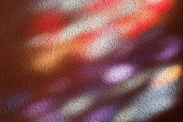 Stained glass window light patches on a church wall stock photo