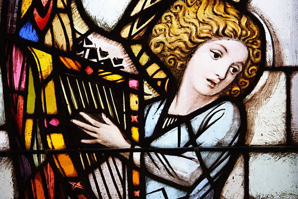 stained glass window of angel playing the harp - harpist stock photos and pictures