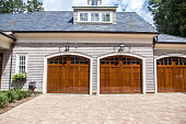 Stained wood custom garage doors for large southern home with curb appeal