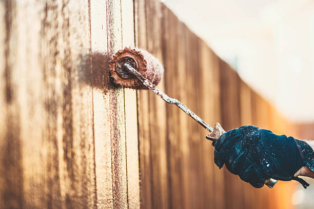 staining a brand new fence. diy home improvement concepts. - houtbeits stockfoto's en -beelden